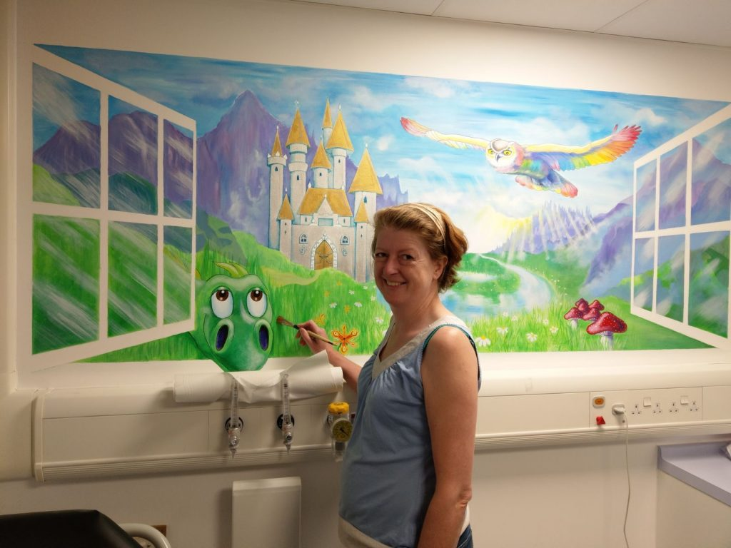 artist painting magical fairytale land in children's hospital room